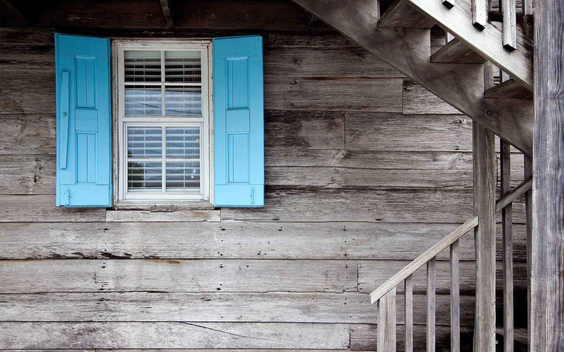 Foto Ventan azul sobre pared de madera